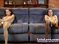 Two adorable girls are masturbating with toys sitting on the one sofa and not paying attention on each other